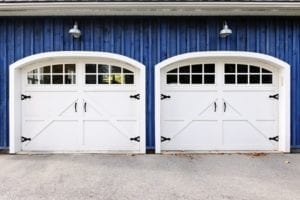 Two white carriage garage doors with windows on blue house