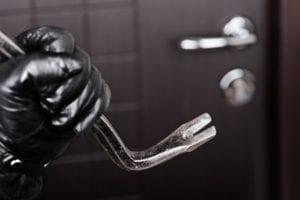 burglar holding a metal crowbar