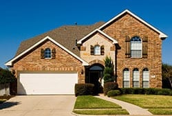 A magnificent and beautiful two-story home with a wooden garage door install by Action Garage Doors repair and replace experts of Bee Cave Texas