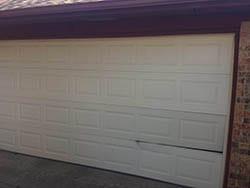 Displaying a home steel garage door in need of repairs in Dallas Texas and being serviced by Action Garage Door Technician 4