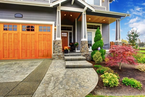 Luxury house entrance porch with stone column trim. View of walkway with landscape