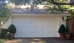 A residential custom wood garage door installation and repair by Action Garage Doors in University Park Texas by technician Katherine