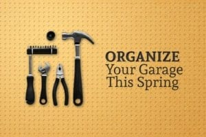 "A hammer, pliers, a wrench, and a screwdriver with a variety of bits hang upon a wall and the words ""Organize Your Garage This Spring"" are written beside them"