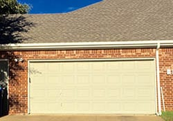 Action Garage Door technicain 3 on a large residential new steel garage door install and repair on a large home in Garland Texas