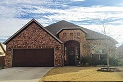 A custom residential wood double car garage door installed and repaired in Mansfield Texas by Adan Vega of Action Garage Doors