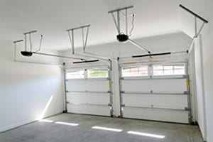 Residential house two car garage interior displaying garage door opener. Action Garage Door repair replace install in Pflugerville a suburb of Austin Texas