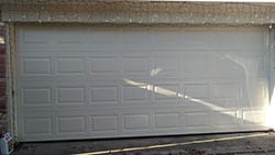 A newly installed steel two car garage door at a home in Plano Texas by Alfredo a top technician with Action Garage Doors