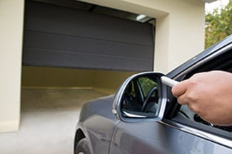 A driver uses his remote to open his garage door