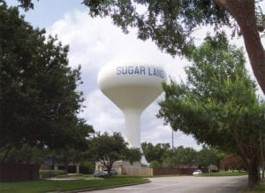 Picture of one of Sugar Land Texas' water towers with a fire station in the background.