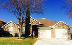 This residential brick veneer home with two single car steel garage doors for repairs and installation in Trophy Club Texas by Action Garage Doors