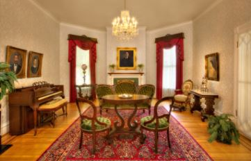 Antique dining set and piano at Fort Bend Museum